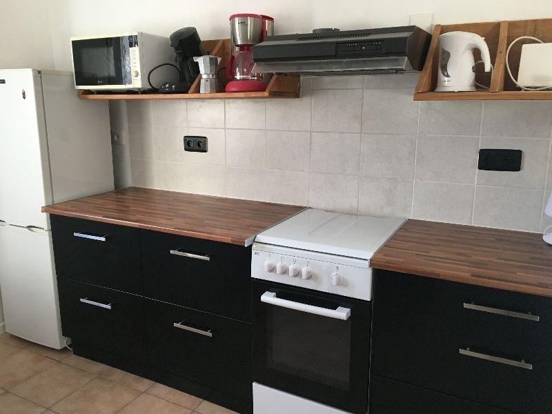 Cuisine côté cuisinière à gaz, et réfrigérateur combiné, avec  encore un grand plan de travail
