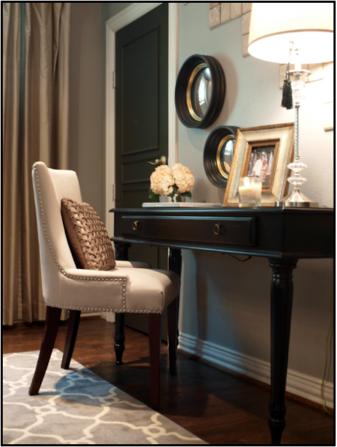 The black door enhances the black desk and round mirror frames.