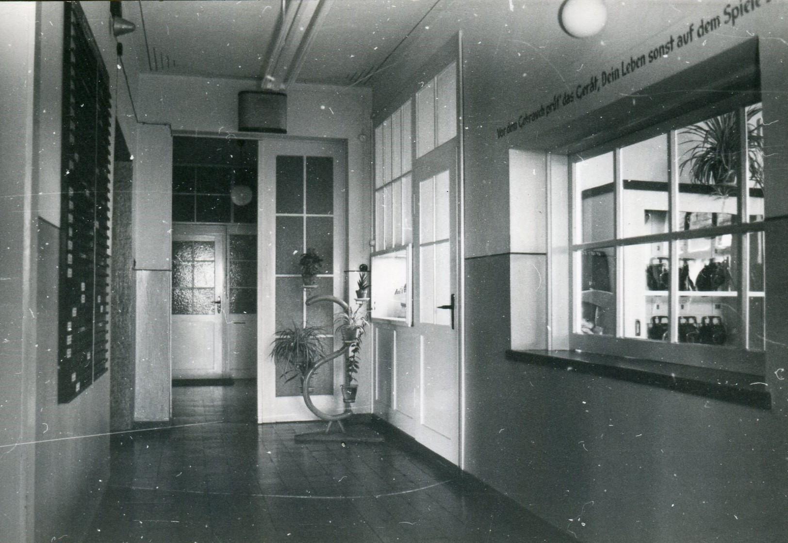 Flur der Grubenrettungsstelle, rechts Ausgabeschalter des Geräteraums, links Anwesenheitstafel der Wehrmitglieder