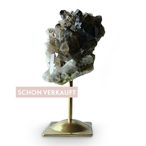 Dekorative Mineralien. Feiner Rauchquarz auf goldfarbenem Metallfuß.