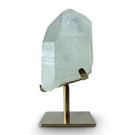 Dekorative Mineralien. Großer Bergkristall auf goldfarbenem Metallfuß.