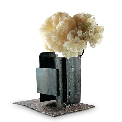 Mineralkunst. Der Zusammenklang der Minerale Stilbit und Apophyllit sind mit schwerem Eisen zu einem Kunstobjekt gearbeitet.