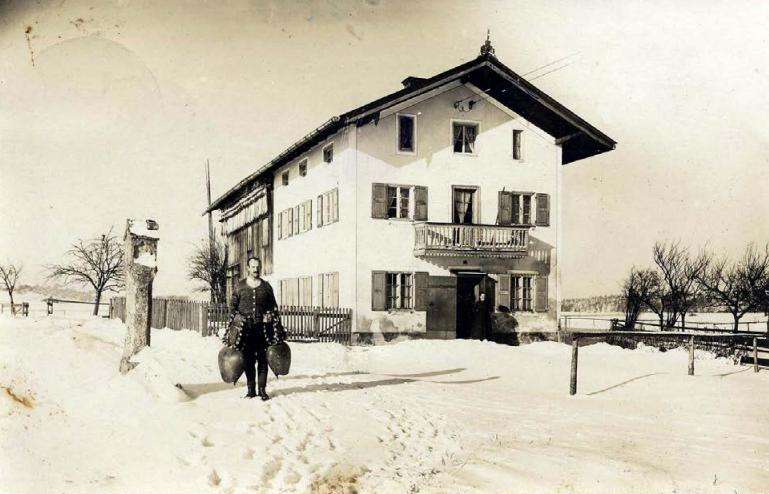 """Die Tuffsäule neben dem """"Fellerkistler""""-Anwesen in Bruck – heute Seehamer Str. 7 und 9, die 1963 in den Straßenunterbau eingearbeitet wurde. Im Vordergrund Anton Zugliani, der damalige Besitzer des Anwesens."""