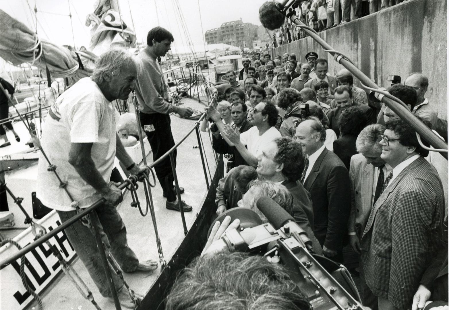 Arrivée de Bernard Moitessier, en compagnie de Pierre Follenfant, sur Joshua, au Grand Pavois 1991 (archives Musée Maritime)