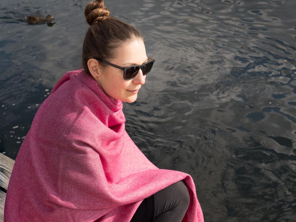 Maxischal/Plaid, Fischgrat, himbeer/naturweiß, von Andelana Alpaka. Sonnenbrille von Kerbholz. Fotografie: Kathrin Häckert