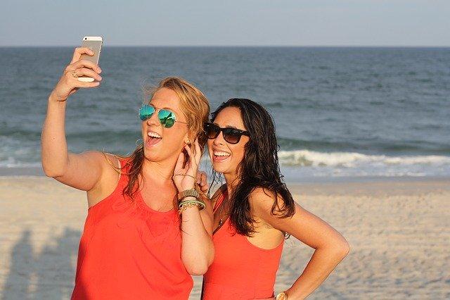 Zwei junge Frauen Teenager am Strand mit Handy beim Selfie machen.