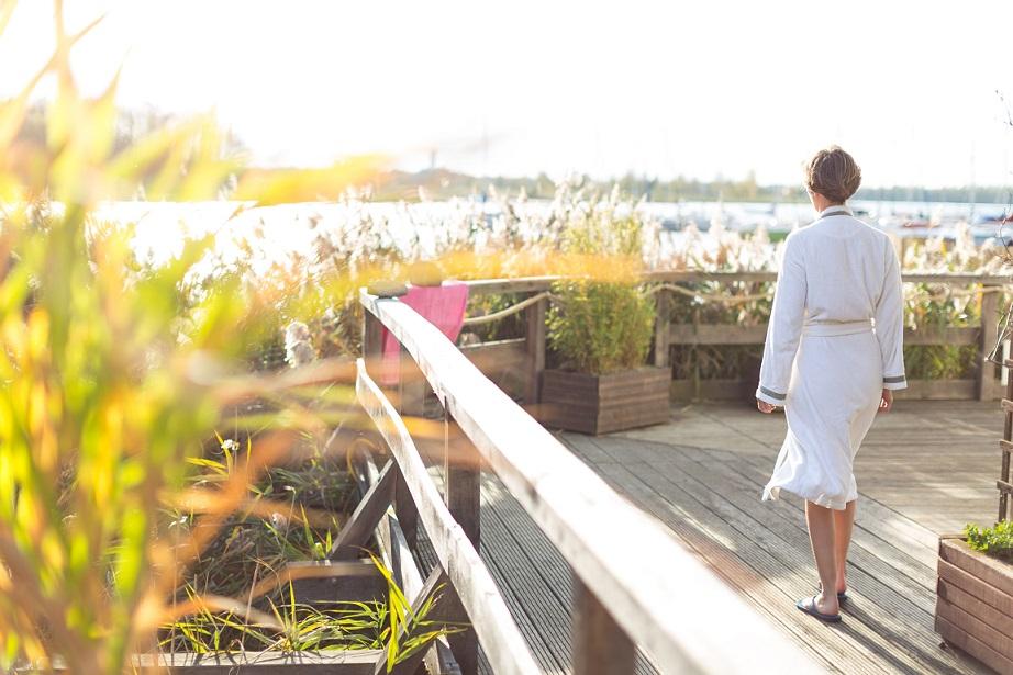 Eine Frau geht in der Morgensonne im Bademantel auf die Hotelterrasse aus Holz und schaut zwischen dem Schilf auf den See