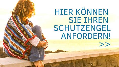 Urlaubsfeeling: Frau mit blonden Haaren und buntem Poncho sitzt auf einer Mauer über dem Meer und schaut in den sonnigen Himmel