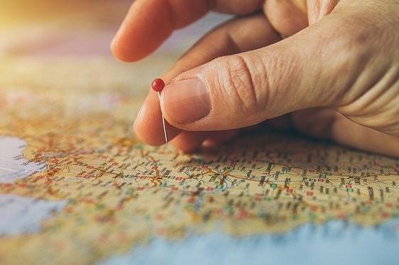 Eine Hand mit Stecknadel über einer Weltkarte bei der Urlaubsplanung.