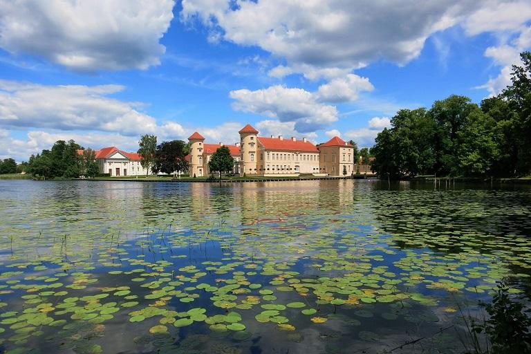 Tourismus-Öffnung nach Corona im land Brandenburg -Schloss Rheinsberg hinter einem See voll von Seerosen