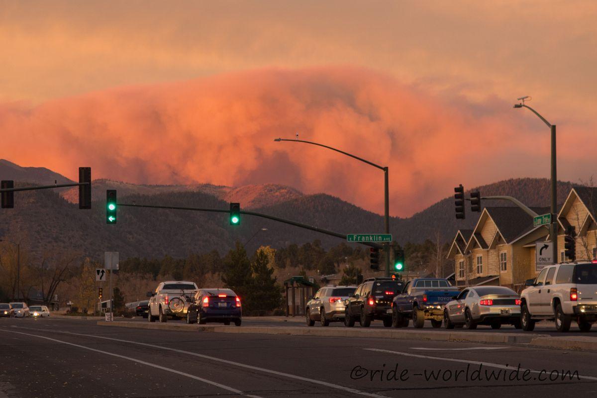 Eine dicke Rauchwolke am Horizont, rot gefärbt von der untergehenden Sonne
