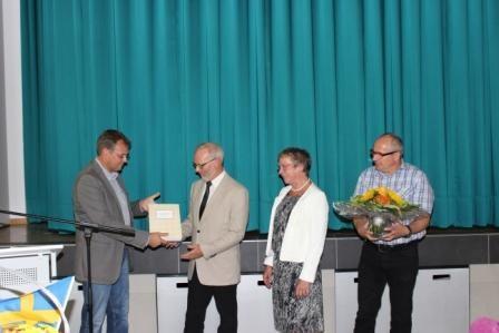 Schulleiter Heinemann überreicht eine Sonderausgabe der Schulchronik....