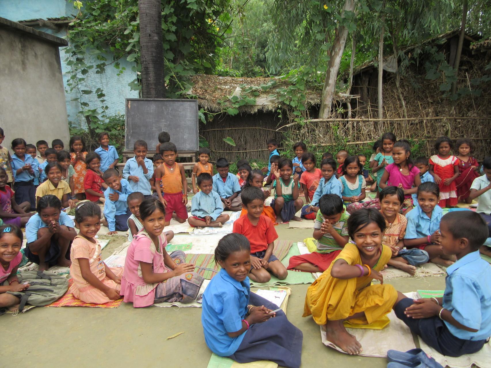 In der Schule gibt es nicht genügend Räume und Schulbänke für alle Kinder-es wird draußen auf Reissäcken sitzend unterrichtet