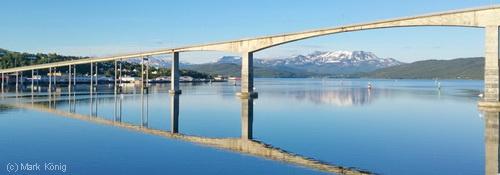 Die Gisundbrua bei Finnsnes spiegelt sich im glatten blauen Wasser