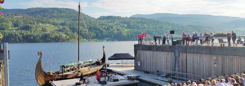 Publikum eines Open-Air Folklore-Konzerts am Seeufer von Notodden mit Wikingerschiff und grünen Hügeln im Hintergrund