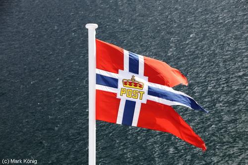 Die wehende Fahne der Hurtigruten-Postschiffe wird nachts eingeholt
