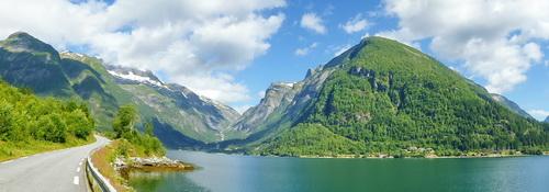 Ein hoher grün bewaldeter Berg ragt in einen blaugrünen Fjord; im Hintergrund Schnee bedeckte Gipfel