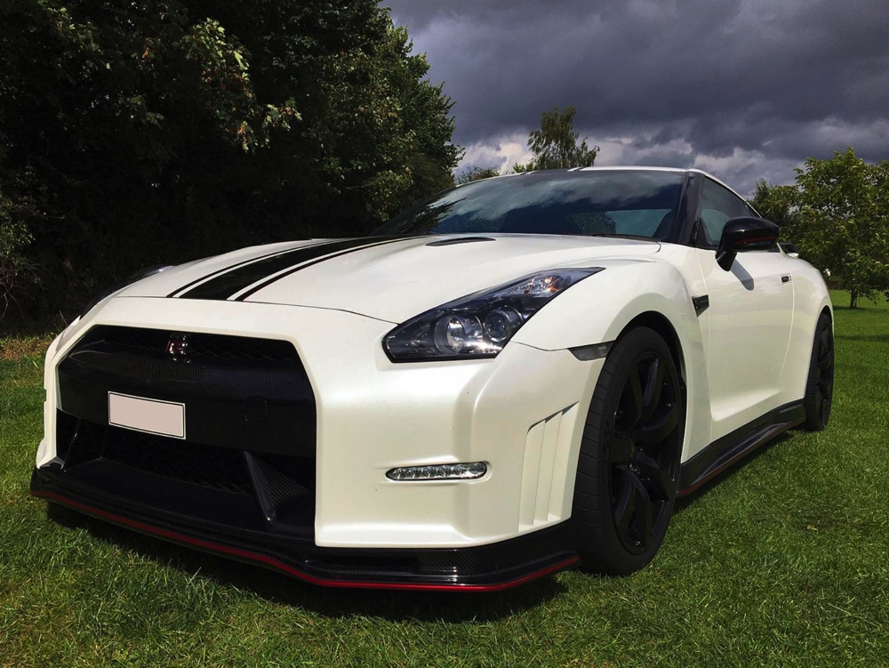 Side view of white Nissan GTR LM750 in field