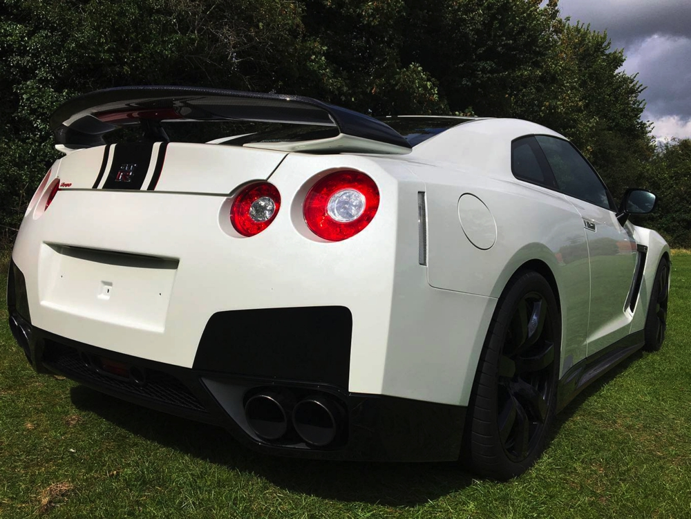 Rear side view of white Nissan GTR LM750 in field