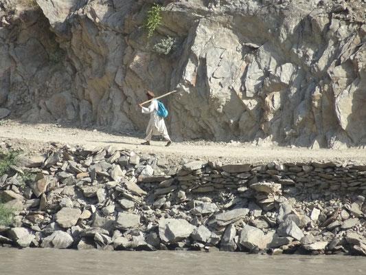 Ein Afghane ist mit einer Schaufel zu Fuss unterwegs. Foto: PK