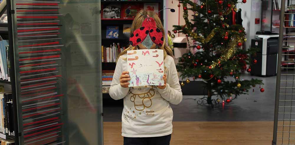 Une jeune fille réalise une couverture de son album Zip à la mer basée sur le livre Zip au marché de l'automne