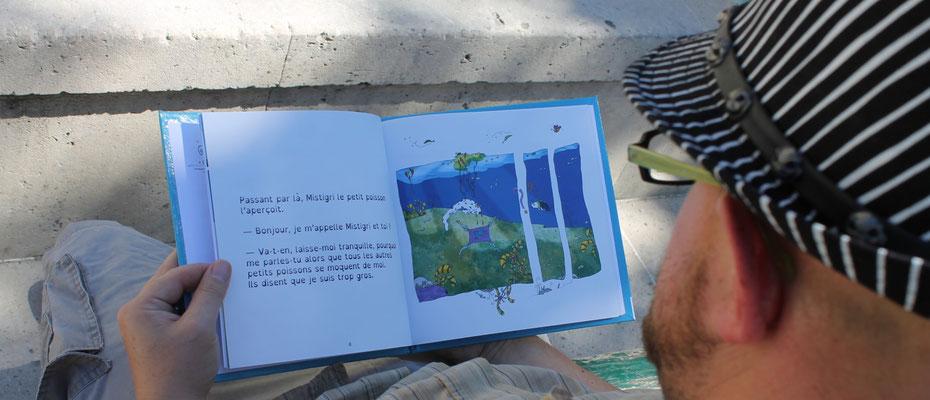 Un lecteur adulte au chapeau pour le livre Faribole et Mistigri sur un banc à Paris