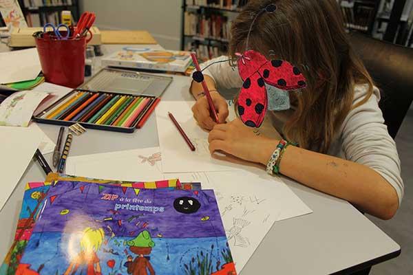 Une jeune fille réalise l'atelier pour créer une couverture d'album basée sur le livre Zip à la fête du printemps