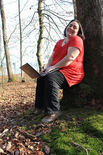 L'illustratrice auteure et graphiste Cloé Perrotin en forêt avec son ordinateur portable