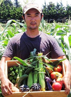 たくさんのお野菜が入ったカゴを持つオーナーの中越節夫さん