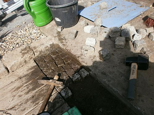 Die noch vorhandenen Lücken werden mit zahlreichen Gehwegsteinen gepflastert
