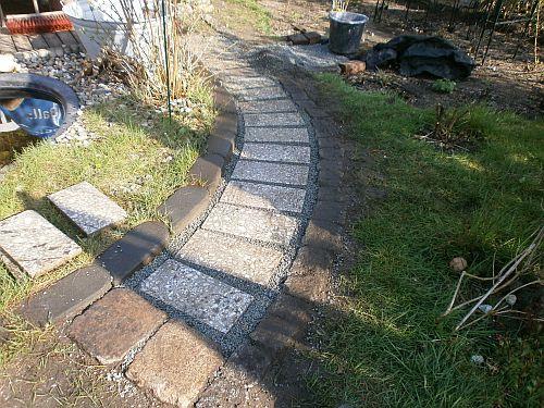 Eine weitere Kiesschicht fixiert und festigt die Wegeplatten
