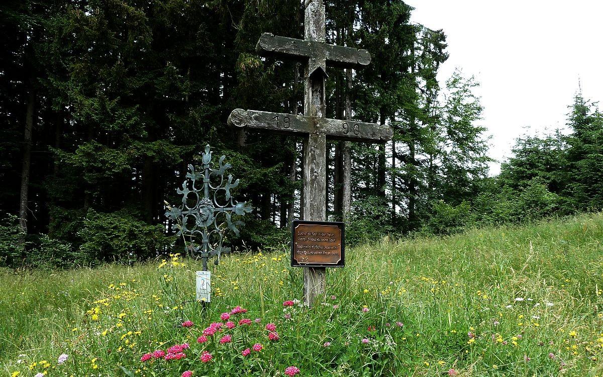 Feldkreuz und Gedenkkreuz am Abstiegspfad durch eine schöne Blumenwiese