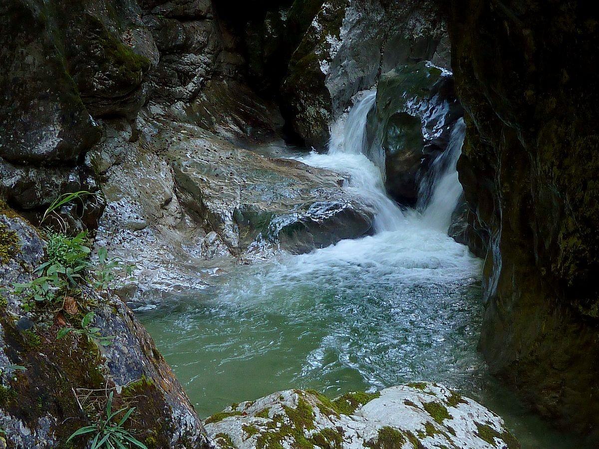 Vom Wasser und mitgeführten Geschiebe und Sand glattpolierte Felsen
