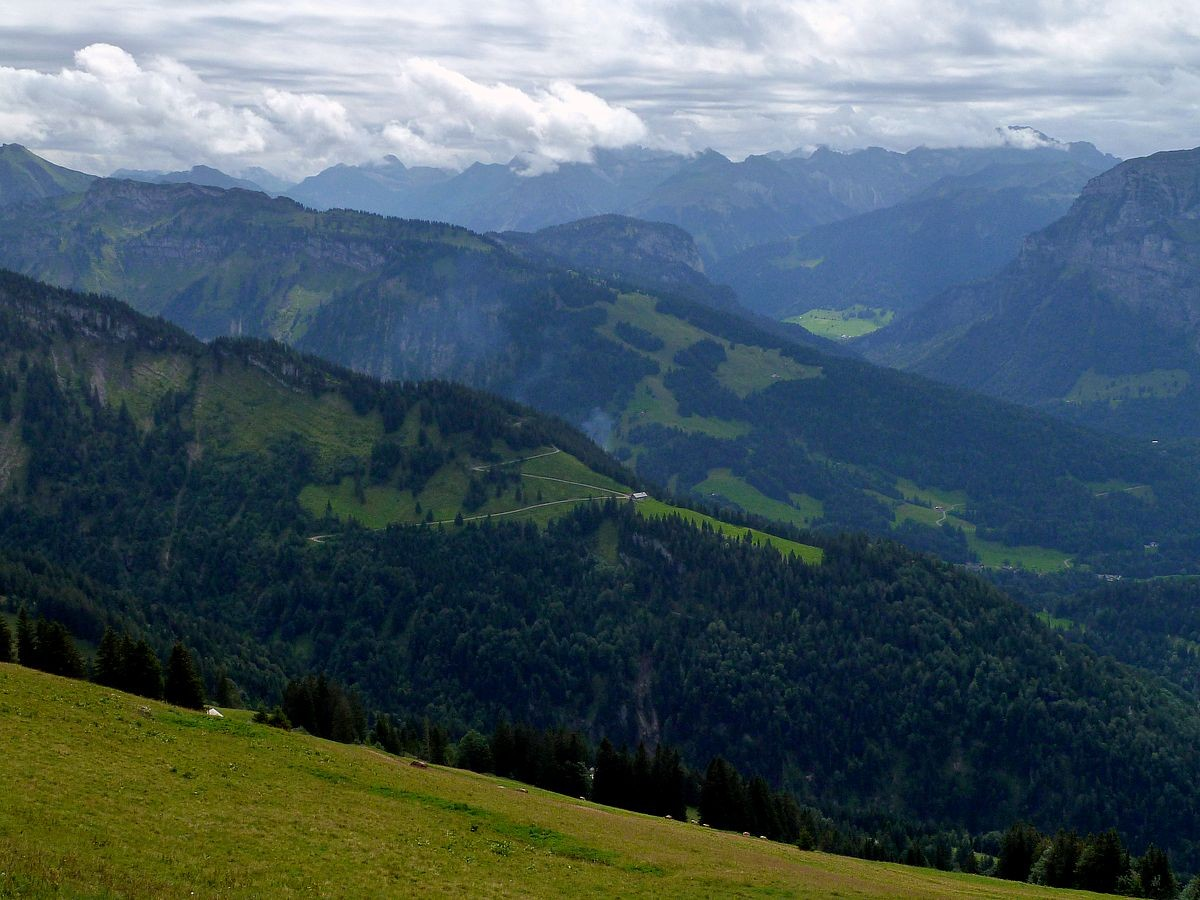 Der Blick über die Mittagsfluh zu den noch wolkenverhangenen hohen Bergen  im  hinteren Bregenzerwald