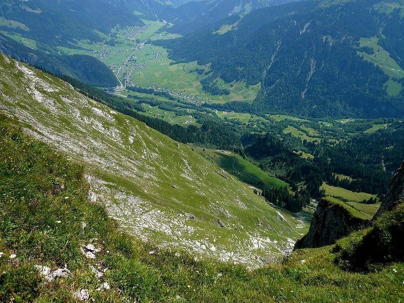 Die hohe, steile südwestlich ausgerichtete Gras- und Schrofenflanke der Kanisfluh. Unten Mitte links die Alpsiedlung Ahorn-Vorsäß und Ortsteile von Au.