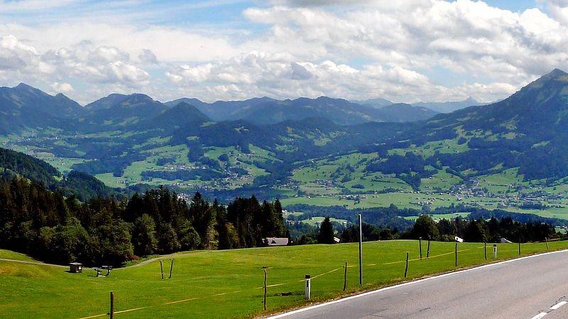Die Bödelestraße mit Blick auf den vorderen Bregenzerwald. Im Hintergrund die Allgäuer Alpen mit Hochvogel, Winterstaude und Niiedere, darunter der Ort Andelsbuch.