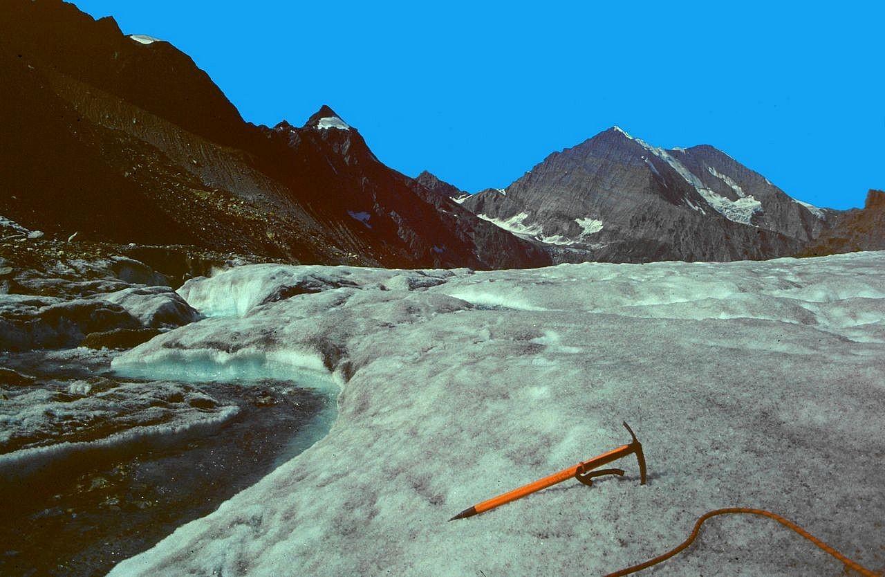 Eisbach am Kanderfirn am Rückweg. Der Eispickel dient zum Größenvergleich. Hinten Hockenhorn und Balmhorn.