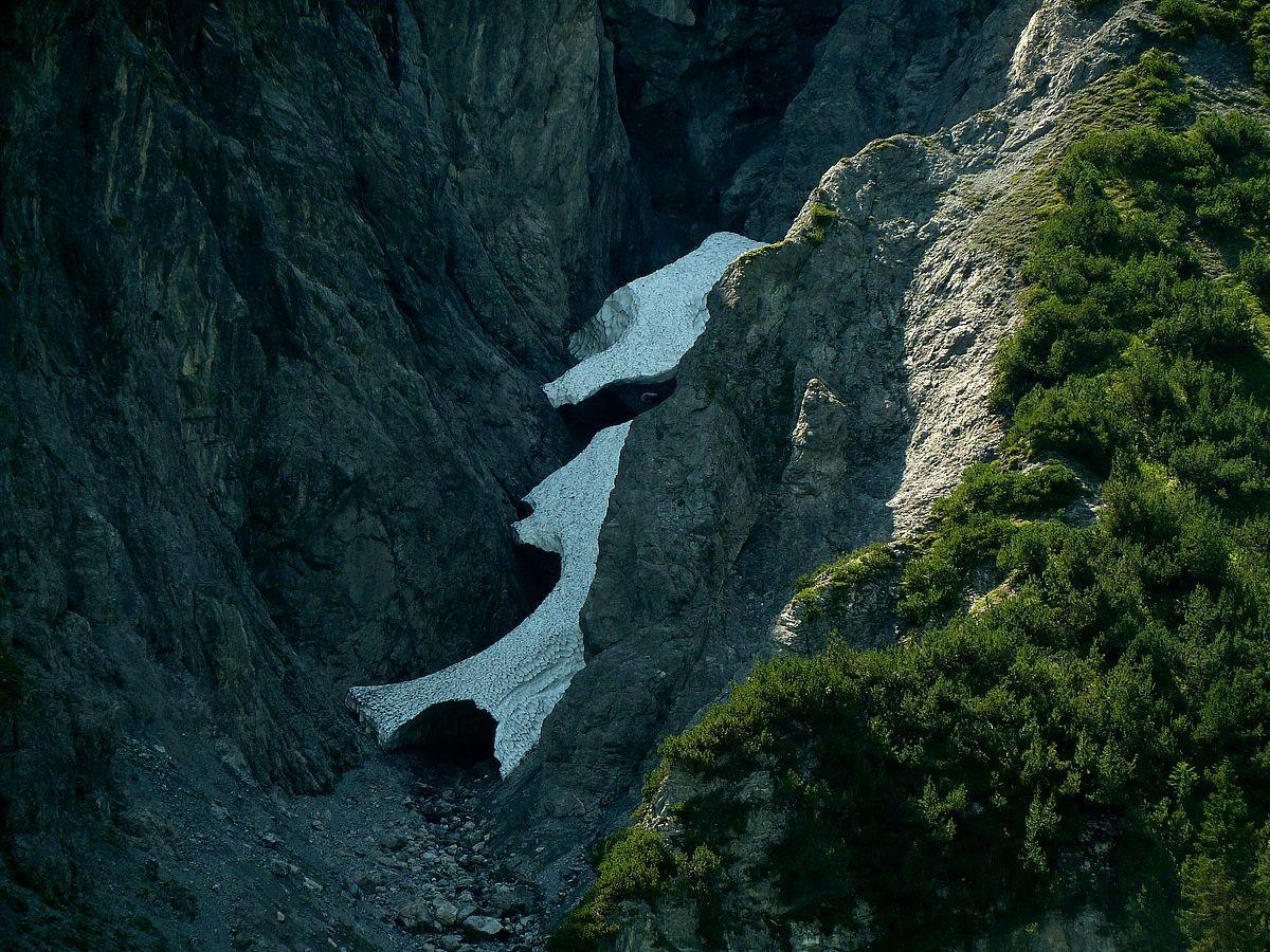 Lawinenschneereste in einer Felsschlucht in der Nordflanke eines Berges bei der Mautstelle zum Formarinsee