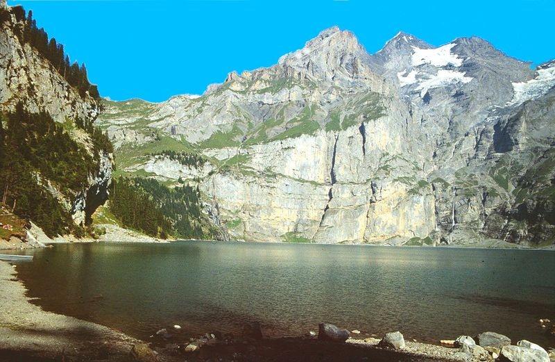Am flachen Ufer des Oeschinensees. Blick zurück ins Alpgebiet von Unterbärgli (links), auf die Wandfluchten mit unterer und oberer Fründenschnur und zur Blümlisalp.