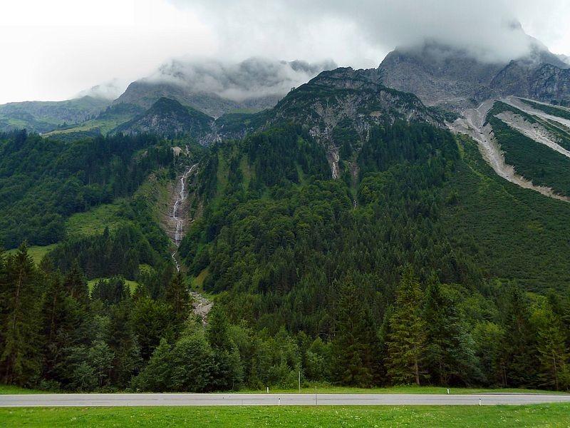 Bregenzerwaldstraße bei Bad Hopfreben. Hochkünzelspitze und Niedere Künzelspitze in Wolken. Links vom Bergbach das Gebiet der Alp Schiedlen.