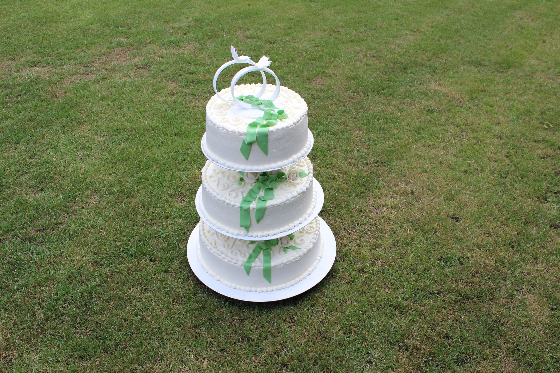 Hochzeitstorte mit Ornamenten aus Sahne, weißen Rosen und farbiger Marzipanschleife. Als Besonderheit statt Brautpaar zwei Ringe in Weiß