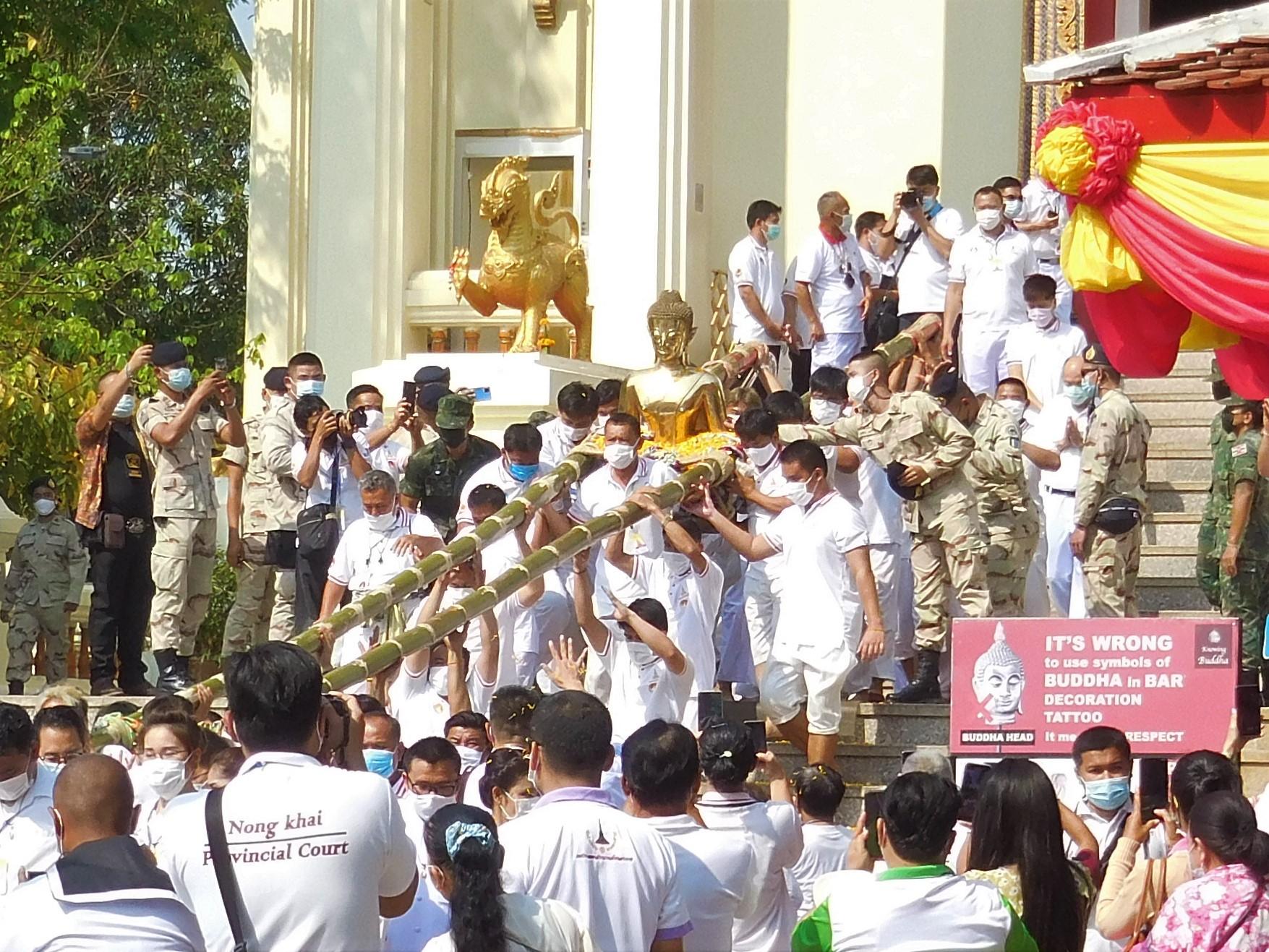 der Buddha wird aus dem Tempel getragen