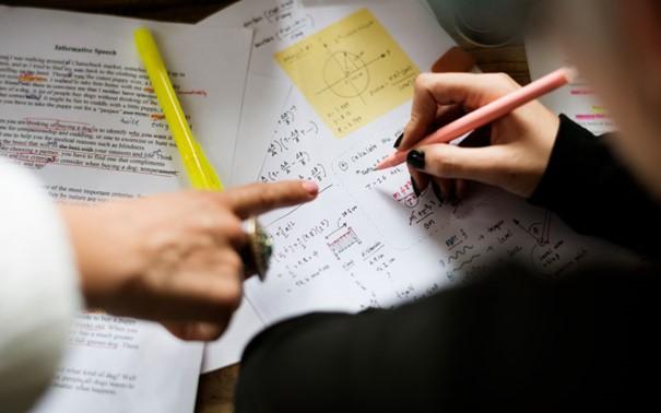 Zwei Personen die Mathe lernen mit Notizen und Lernzetteln.
