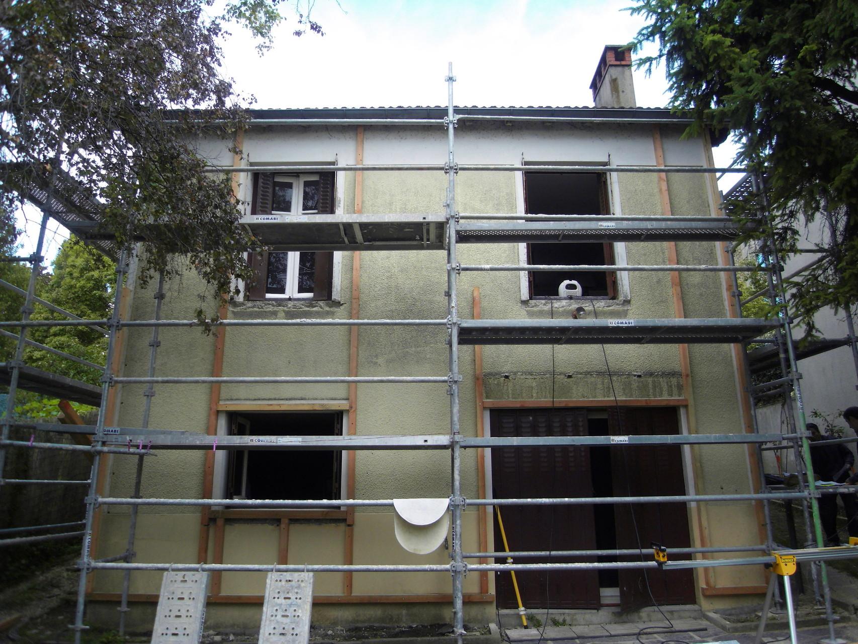 après piochage des appuis des fenêtre, pose de l'ossature bois qui permet de rattrapper les différences de niveau (sous-bassement, bandeaux, encadrements de fenêtres)