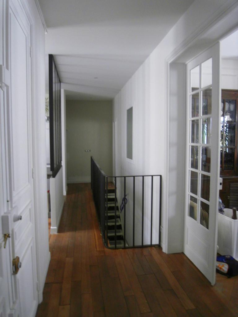 un grand couloir lumineux, un escalier fin