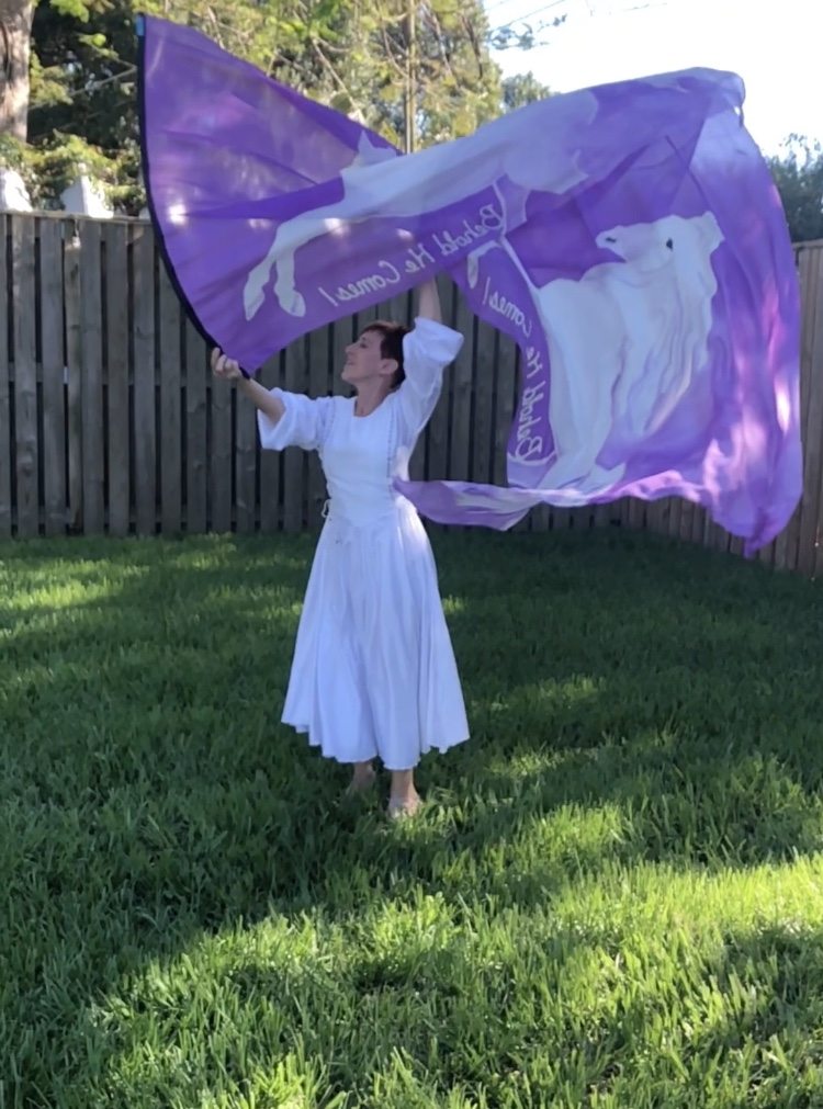 Silk flag with white horse rearing on a purple background.