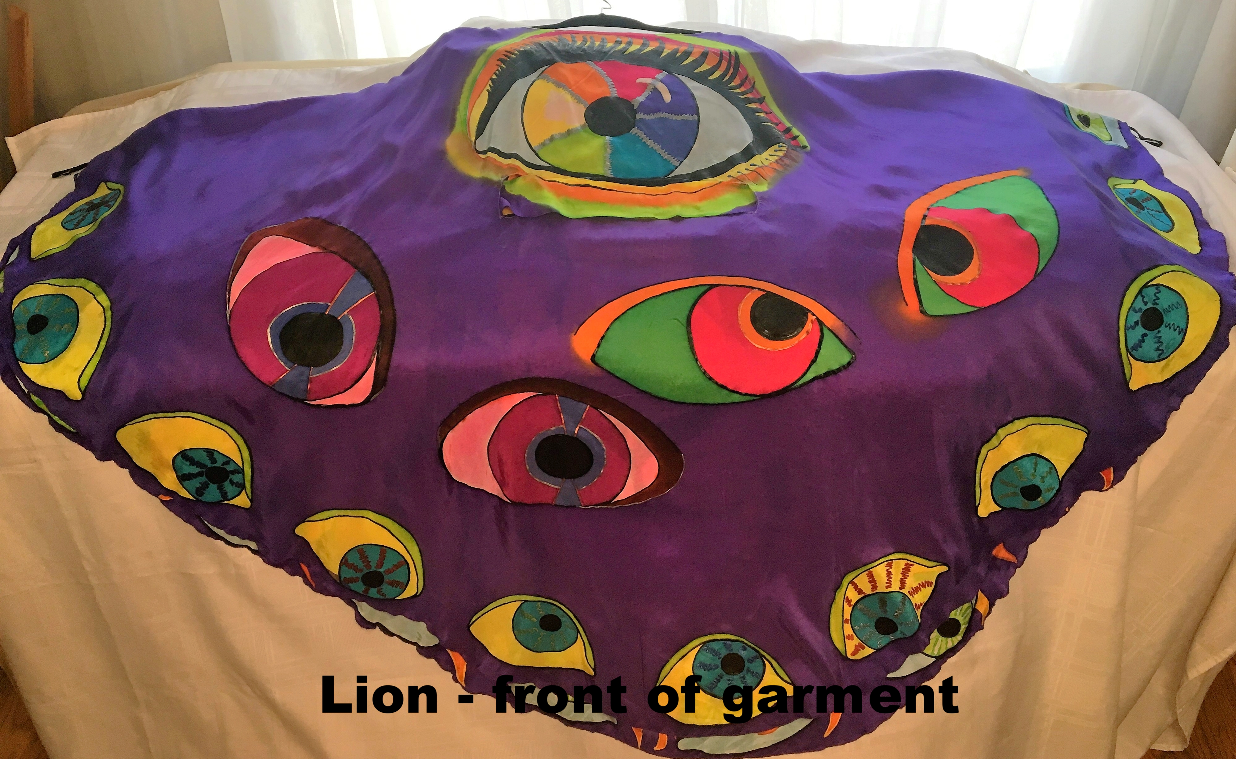 Purple cape garment showing a big eye and many small eyes