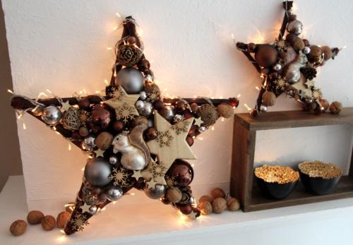 Großer Leucht-Stern mit kleinem Stern, Teelichtern und Walnüssen als Deko auf dem Kaminsims.