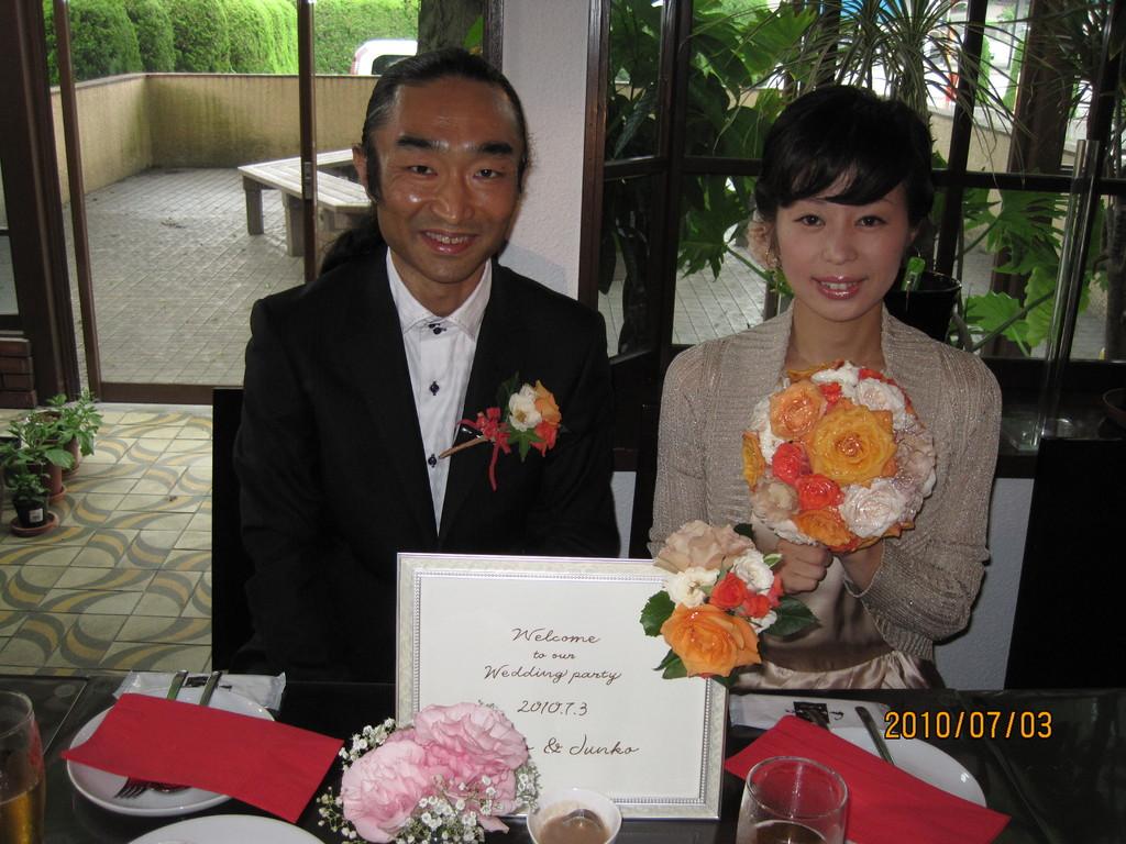 オレンジ~ベージュのグラデーションブーケ。同じお花を使ったウエルカムボード。お二人の笑顔が素敵ですね。