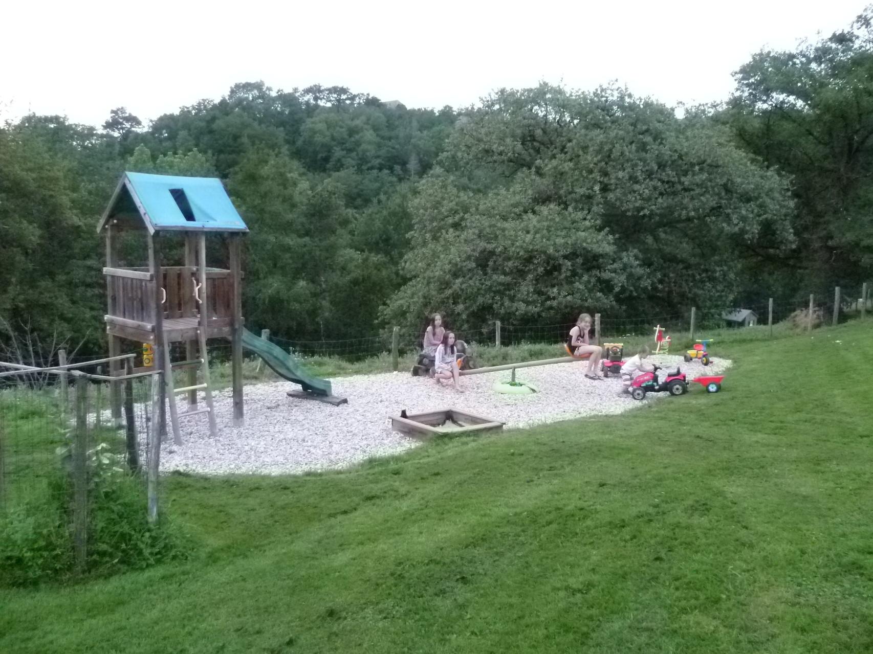 Aire de jeux : toboggan, jeu à ressort, balançoire, bac à sable, tracteurs à pédales, cabane